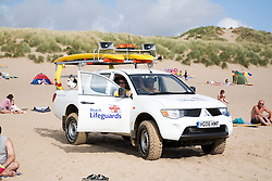 RNLI Lifeguard in his vehicle on the beach,