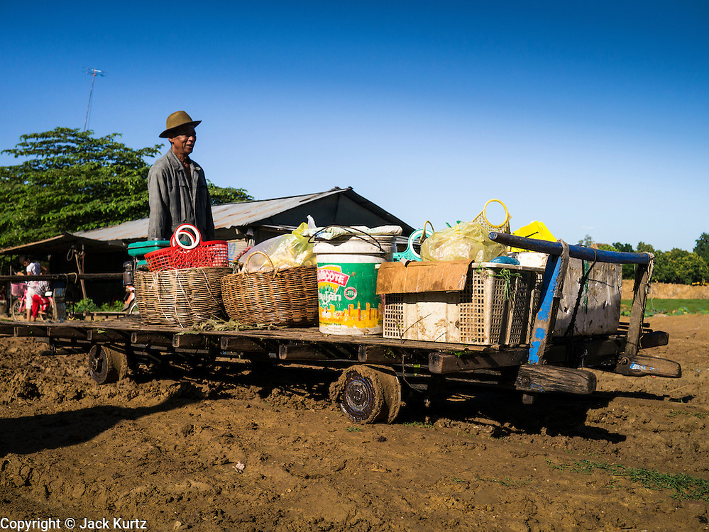 29 JUNE 2013 - BATTAMBANG, CAMBODIA:  A bamboo train driver pushes his train, loaded with supplies from a market, to a waiting customer. The bamboo train, called a norry (nori) in Khmer is a 3m-long wood frame, covered lengthwise with slats made of ultra-light bamboo, that rests on two barbell-like bogies, the aft one connected by fan belts to a 6HP gasoline engine. The train runs on tracks originally laid by the French when Cambodia was a French colony. Years of war and neglect have made the tracks unsafe for regular trains.  Cambodians put 10 or 15 people on each one or up to three tonnes of rice and supplies. They cruise at about 15km/h. The Bamboo Train is very popular with tourists and now most of the trains around Battambang will only take tourists, who will pay a lot more than Cambodians can, to ride the train.       PHOTO BY JACK KURTZ