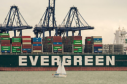 © Licensed to London News Pictures. 14/10/2021. Felixstowe, UK. The Evergreen cargo ship is docked at The Port of Felixstowe that has had to turn away ships from Asia because of a backlog of containers not being distributed due to the  shortage of HGV drivers. AP Moller-Maresk, the worlds largest container company has had to load containers onto smaller ships bound for the UK. This is having a disruptive effect as the shipping industry enters the pre-Christmas period of delivery with a possible shortage of Christmas goods being sold in the UK. Photo credit: London News Pictures