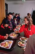 Teen serving couple Christmas dinner in church soup kitchen.  Minneapolis Minnesota USA