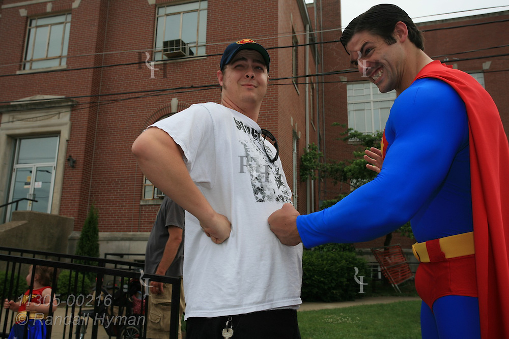 Official Superman of Superman Celebration, Josh Boultinghouse, pretends to punch man in stomach who doesn't flinch; Metropolis, Illinois.