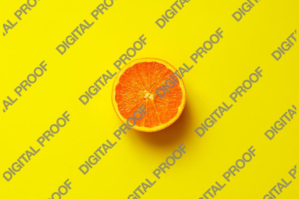 Orange fruit. Orange half fruit sliced isolate on yellow background seen from above flatlay style, close up.