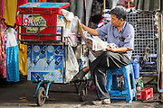 06 JUNE 2013 - BANGKOK, THAILAND:     A vendor reads his newspaper in Bobae Market in Bangkok. Bobae Market is a 30 year old market famous for fashion wholesale and is now very popular with exporters from around the world. Bobae Tower is next to the market and  advertises itself as having 1,300 stalls under one roof and claims to be the largest garment wholesale center in Thailand.       PHOTO BY JACK KURTZ