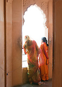 Women at a window looking out from a window at Mehrangarh Fort in the city of Jodhpur, Rajasthan, India