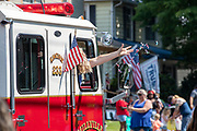 A woman throws candy from a fire truck during the Independence Day parade in Millville, Pennsylvania on July 5, 2021.