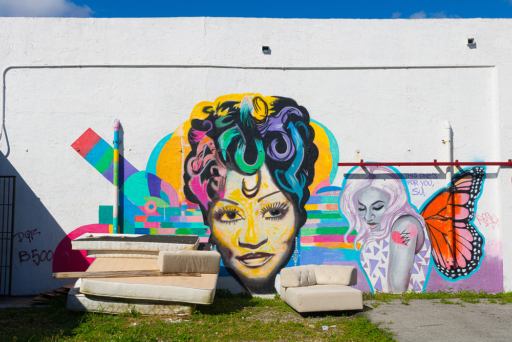 Mural portrait of an African-American woman, plus a second woman with butterfly wings, on a wall amongst old couches in Miami's Wynwood district