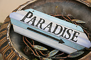 weathered wooden sign with an arrow pointing right to paradise