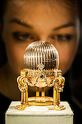 A newly discovered Fabergé Egg on display at jewellers Wartski, who arranged its sale to a private collector. Here it is examined by Madalena Zdziebkowska an employee of Wartski.  It will be on public view for the first time in over 100 years until Thursday, 17th April (11am to 5pm). Grafton Street, London UK, 7th April 2014.