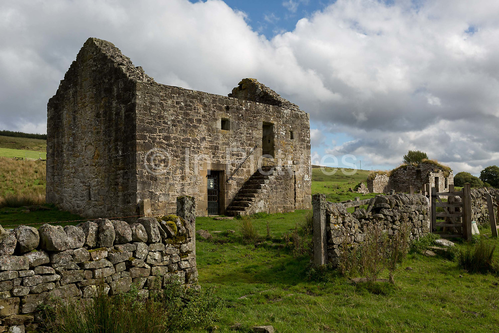 Exterior of the best preserved Grade 2 listed Bastle a fortified 18th/19th century farmhouse at Black Middens, on 28th September 2017, in Gatehouse, Northumberland, England. Bastel, bastle, or bastille houses are a type of construction found along the Anglo-Scottish border, in the areas formerly plagued by border Reivers. Typically, the bastle was 10-12 metres long by 5-6 metres wide with walls up to 1.6 metres thick. Some 400 tonnes of sandstone blocks were needed for construction with corner quoins corner stones weighing up to 300kg. Bastles would have been costly to build so afforded by only wealthy families fearing attack by cross-border bandits.