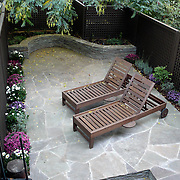 Small Brooklyn Garden designed and built by Outside Space NYC for young family. It features Irregular Blue Stone paving with stacked stone seating wall, Cedar Lattice Fence and dramatic outdoor lighting.