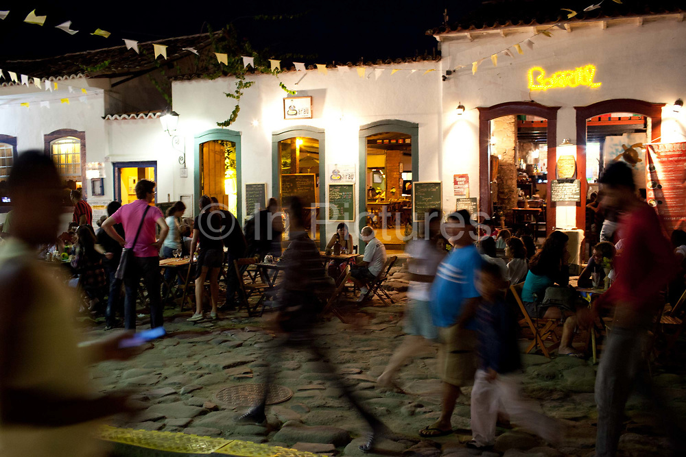 People eating, drinking and walking around in the evening, Paraty, night shot with colourful lighting, Rio de Janeiro State, Brazil.