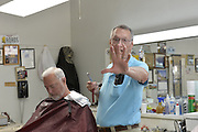 "4/8//16 Canton, MS. With a straight razor and towel in hand barber Bobby Chandler says he will not serve any LGBT people. Days after Mississippi Governor Phil Bryant  signed a controversial ""religious freedom"" bill into law, Bobby Chandler of Chandler O'Cain barber shop in Canton Mississippi says he will not  serve any LGBT people. Mr. Chandler pictured in a blue shirt working on a customer has been in business in the same space for over 30 years.  Danny O'Cain Chandlers business partner is pictured on the right in the pink shirt. Photo ©Suzi Altman"