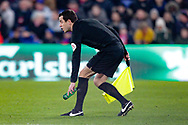 Assistant referee Lee Betts picks up a bottle thrown on the pitch by the Grimsby Town fans after the sending off of Grimsby Town defender Andrew Fox (19) during the The FA Cup 3rd round match between Crystal Palace and Grimsby Town FC at Selhurst Park, London, England on 5 January 2019.