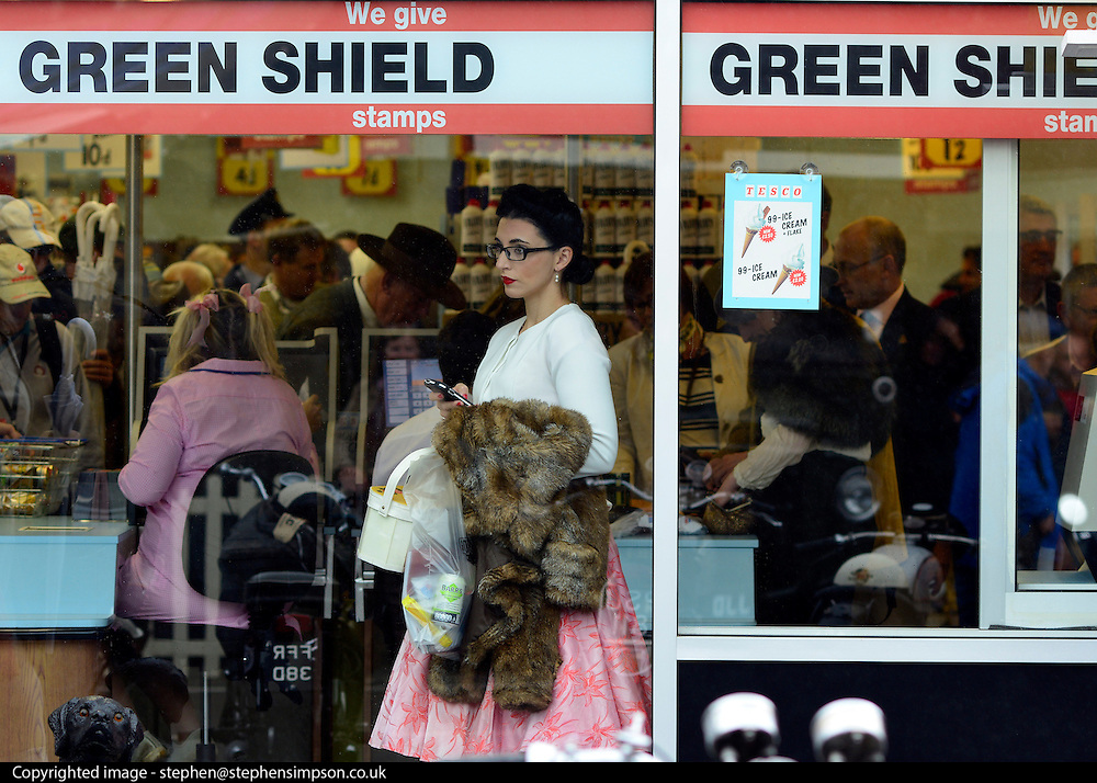 © Licensed to London News Pictures. 14/09/2012. Goodwood, UK A woman looks out of a window as people shop in a fully stocked vintage Tesco supermarket store. People enjoy the atmosphere at the 2012 Goodwood Revival Meeting today 14 September 2012. Participants are encouraged to dress in period dress.. Photo credit : Stephen Simpson/LNP