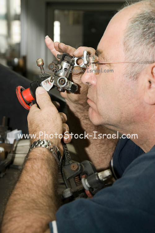 Israel, Interior of a diamond cutting and polishing workshop. A workers work station a worker inspecting the diamond with a magnifying glass