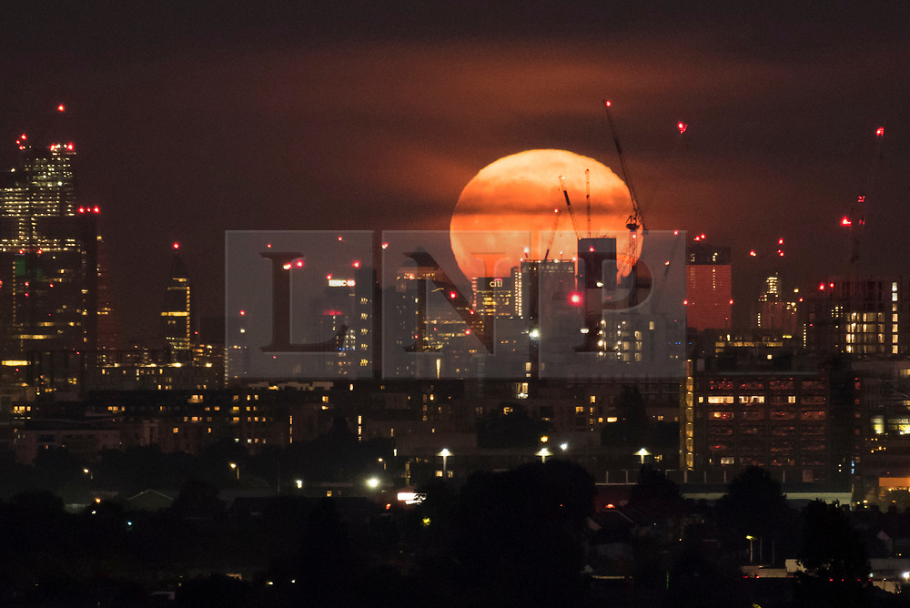 © Licensed to London News Pictures. 14/09/2019. LONDON, UK.  The full moon rises over the City of London, as seen from Northolt to the west of the capital.  This month's full moon is known as the Harvest Moon, as it is the closest full moon to the autumnal equinox.  Photo credit: Stephen Chung/LNP