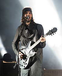 """© London News Pictures. 25/08/2012. Reading, UK. Guitarist Sergio """"Serge"""" Pizzorno performing with Kasabian on Day two of Reading Festival 2012 in Reading, Berkshire, UK on August 25, 2012. The three day event which attracts over 80,000 music fans opens officially today (Friday) and will headline The Cure, Kasabian and The Foo Fighters Photo credit : Ben Cawthra/LNP"""