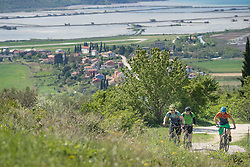 Bikers riding bikes while houses and lakes in background