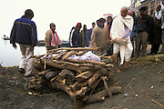 The main mourner, dressed in white, lights the pyre during the cremation of his father on Manikarnika Ghat in Varanasi, India, in January 2004.