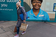Carrying a bag with the words We love the way you live, a lady walks past the hoarding featuring the face of an NHS Staff Nurse employed at University College London, on 25th January 2018, in London, England.