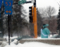 A person dressed in a statue of liberty costume on a street corner advertises the services of a local business