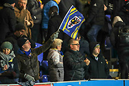 AFC Wimbledon fan waving flag during the EFL Sky Bet League 1 match between AFC Wimbledon and Doncaster Rovers at the Cherry Red Records Stadium, Kingston, England on 14 December 2019.