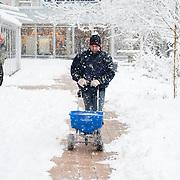 Nederland, Rotterdam, 17 december 2010. Weeralarm, zware sneeuwval in de Randstad. Medewerkers van bejaardentehuis Humanitas, gekleed in dikke winterkleding en mutsen, maken het trottoir naar de ingang van het ouderenhuis vrij van sneeuw. Door middel van het strooien van zout houden ze het pad schoon van sneeuw. Wegscheppen van sneeuw, pad maken in de sneeuw. Foto: David Rozing