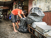 14 SEPTEMBER 2015 - BANGKOK, THAILAND:  A man goes through his belongings while he removes his belongings from the home he's being evicted from. Fiftyfour homes around Wat Kalayanamit, a historic Buddhist temple on the Chao Phraya River in the Thonburi section of Bangkok are being razed and the residents evicted to make way for new development at the temple. The abbot of the temple said he was evicting the residents, who have lived on the temple grounds for generations, because their homes are unsafe and because he wants to improve the temple grounds. The evictions are a part of a Bangkok trend, especially along the Chao Phraya River and BTS light rail lines. Low income people are being evicted from their long time homes to make way for urban renewal.           PHOTO BY JACK KURTZ