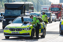 A Surrey Police officer prepares to operate a drone after Insulate Britain climate activists blocked the M25 between Junctions 9 and 10 on 21st September 2021 in Ockham, United Kingdom. Activists briefly halted traffic on both carriageways of the motorway as part of a campaign intended to push the UK government to make significant legislative change to start lowering emissions before being removed and arrested by Surrey Police.