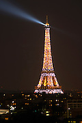 The Eiffel Tower in Paris illuminated at night against a dark blue black sky, search light ray on the sky, illumination golden yellow and glittering special effects white blinking light Paris France
