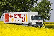 Europe, Germany, North Rhine-Westphalia, Ruhr area, street through rape fields between Essen and Bochum, truck of the company REWE [the supermarkets of the REWE Group will be supplied daily with food]. ....Europa, Deutschland, Nordrhein-Westfalen, Ruhrgebiet, Strasse durch Rapsfelder zwischen Essen und Bochum, LKW der Firma REWE [die Supermaerkte der REWE Group werden taeglich mit Lebensmittel beliefert].