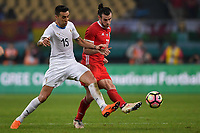 """Gareth Bale, right, of Wales national football team kicks the ball to make a pass against Matias Vecino of Uruguay national football team in their final match during the 2018 Gree China Cup International Football Championship in Nanning city, south China's Guangxi Zhuang Autonomous Region, 26 March 2018.<br /> <br /> Edinson Cavani's goal in the second half helped Uruguay beat Wales to claim the title of the second edition of China Cup International Football Championship here on Monday (26 March 2018). """"It was a tough match. I'm very satisfied with the result and I think that we can even get better if we didn't suffer from jet lag or injuries. I think the result was very satisfactory,"""" said Uruguay coach Oscar Tabarez. Wales were buoyed by a 6-0 victory over China while Uruguay were fresh from a 2-0 win over the Czech Republic. Uruguay almost took a dream start just 3 minutes into the game as Luis Suarez's shot on Nahitan Nandez cross smacked the upright. Uruguay were dealt a blow on 8 minutes when Jose Gimenez was injured in a challenge and was replaced by Sebastian Coates. Inter Milan's midfielder Matias Vecino of Uruguay also fired at the edge of box from a looped pass but only saw his attempt whistle past the post. Suarez squandered a golden opportunity on 32 minutes when Ashley Williams's wayward backpass sent him clear, but the Barca hitman rattled the woodwork again with goalkeeper Wayne Hennessey well beaten."""