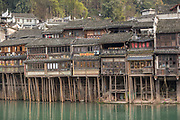 Architectural photograph with view of stilted houses in an ancient Chinese town along the Tuojiang River, Fenghuang, Hunan Province, China