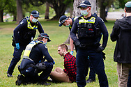A man is seen being questioned by police after failing to provide his details during the Freedom protest on October 23, 2020 in Melbourne, Australia. Freedom protests are being held in Melbourne in response to the governments COVID-19 restrictions and continuing removal of liberties despite new cases being on the decline. Victoria recorded a further 1 new cases overnight along with no deaths recorded.(Photo by Mikko Robles/Speed Media)