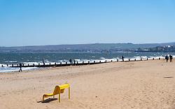 Portobello beach and promenade near Edinburgh during Coronavirus lockdown on 19 April 2020. Empty beach with single yellow bench.