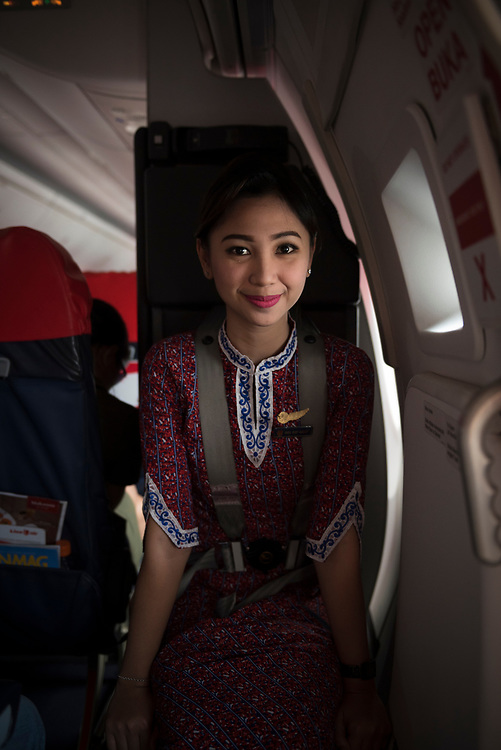 Yogyakarta, Indonesia - March 25, 2017: A flight attendant on Lion Air sits buckled into her seat next to the emergency exit just before landing in Yogyakarta, Indonesia.