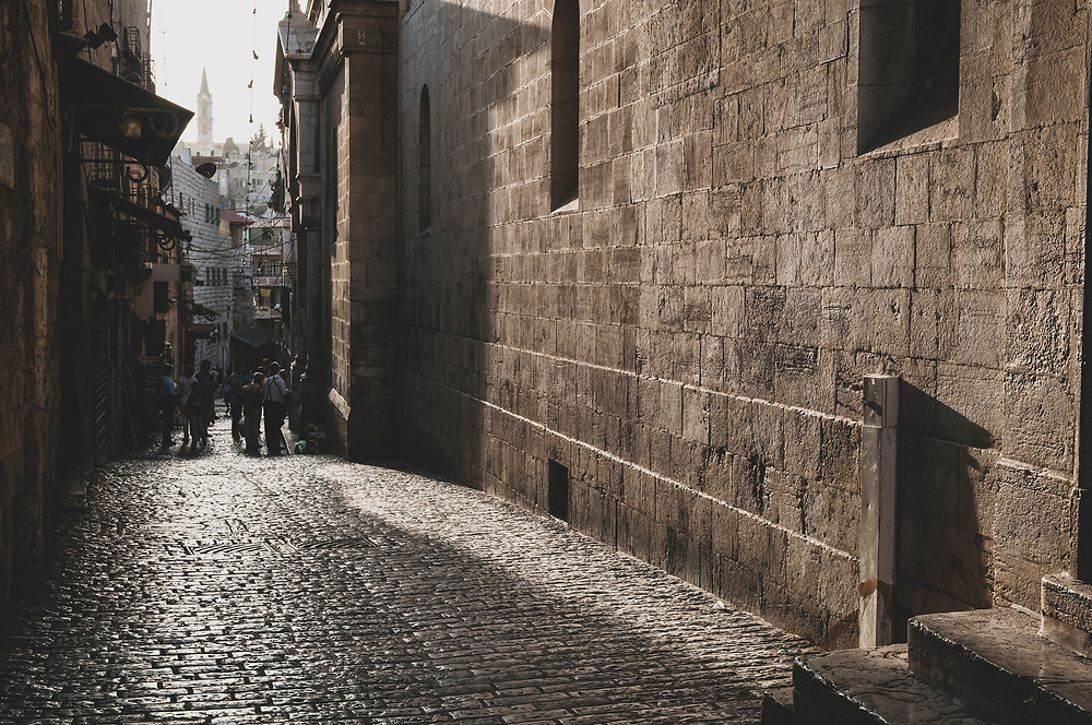 Jerusalem - October 19, 2010:  People stand on Lion's Gate Street, between a souvenir shop and an entrance to a Greek Orthodox monastery said to be the prison of Christ, on the Via Dolorosa.