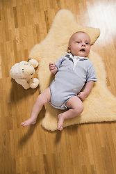 Baby boy laying on wooden floor