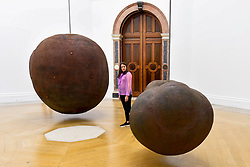 "© Licensed to London News Pictures. 17/09/2019. LONDON, UK. A visitor views ""Body"", 1991/93, and ""Fruit"", 1991/93, both by Antony Gormley. Preview of a new exhibition by Antony Gormley at the Royal Academy of Arts.  The show bring together existing and specially conceived new works from drawing to sculptures to experimental environments to be displayed in all 13 rooms of the RA's Main Galleries 21 September to 3 December 2019.  Photo credit: Stephen Chung/LNP"