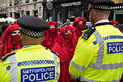 Members of the Extinction Rebellion Red Rebel Brigade line up in front of Metropolitan Police officers in the Covent Garden area during the first day of Impossible Rebellion protests on 23rd August 2021 in London, United Kingdom. Extinction Rebellion are calling on the UK government to cease all new fossil fuel investment with immediate effect.