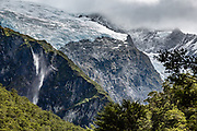 Below Rob Roy Glacier, wind blows multiple wisps of a waterfall back upwards. Rob Roy Track, Mount Aspiring National Park, Southern Alps, Otago region, South Island of New Zealand. In 1990, UNESCO honored Te Wahipounamu - South West New Zealand as a World Heritage Area.