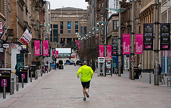 Glasgow, Scotland, UK. 26 March, 2020. Views from city centre in Glasgow on Thursday during the third day of the Government sanctioned Covid-19 lockdown. The city is largely deserted. Only food and convenience stores open. Pictured; Jogger runs along an empty Buchanan Street. Iain Masterton/Alamy Live News