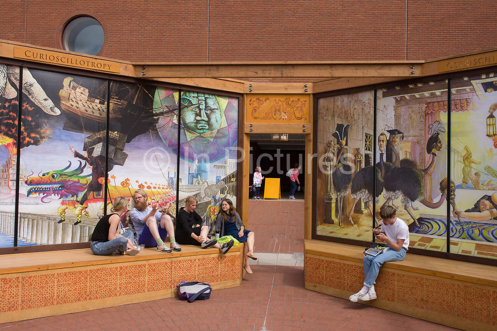 """The artwork entitled Crossroads of Curiosity by David Normal, outside the British Library, London. Londoners rest on the flat surfaces below scenes, encouraged to scan the murals using cameras on a phone to call up the collage source material on the phone's screen and then interact with the artist's interpretations. The official descriiption says of the artwork: """"Artist David Normal's Crossroads of Curiosity is a suite of murals that extends the notion of a """"cabinet of curiosity"""" outward from the rectilinear arrangement of objects in glass cases to encompass the world in a series of dramatic tableaux featuring provocative juxtapositions of vastly different times, places, and peoples."""""""