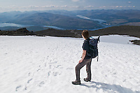 Single female hiker takes in view of Loch Linnhe from near summit of Ben Nevis, Scotland's highest mountain