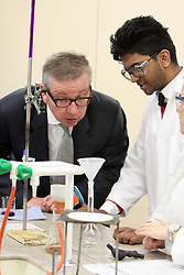 ©Licensed to London News Pictures. 04/04/2014<br /> Brooke Weston Academy, Corby, Northamptonshire. Secretary of State for Education Michael Gove MP visiting Brooke Weston Academy in Corby as part of a fact finding tour of free schools. Pictured, Michael Gove MP in Year 12 chemistry lesson with Sam Hussain.<br /> Photo credit: Steven Prouse/ LNP
