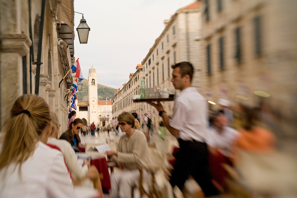 Europe, Croatia, Dalmatia, Dubrovnik.  Outdoor cafe on the Stradun (also known as Placa), the main street which crosses the old city. The historic center of Dubrovnik is a UNESCO World Heritage site.