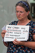 A woman holds a sign relating to suspended members of North-West Cambridgeshire and Peterborough CLPs at a protest lobby outside the Labour Partys headquarters by supporters of left-wing Labour Party groups on 20th July 2021 in London, United Kingdom. The lobby was organised to coincide with a Labour Party National Executive Committee meeting during which it was asked to proscribe four organisations, Resist, Labour Against the Witchhunt, Labour In Exile and Socialist Appeal, members of which could then be automatically expelled from the Labour Party.