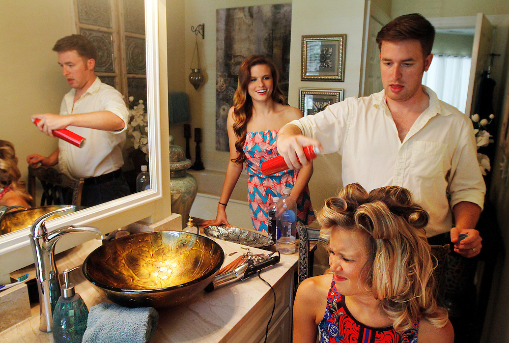 Jeremy Culpepper, Executive Director of the Miss Hilton Head Island Scholarship Organization, styles the hair of Miss Hilton Head Island 2014 Rachel Tripp, right, as Miss Hilton Head Island Teen 2014 Amanda Compton, center, watches in the background. The girls had a send-off party at the home of Lisa Bryant (board member) in Palmetto Hall on June 7, 2014.