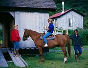 Heather and Lee Robbins with Lori Egge on horse, Raspberry Island Lodge, Raspberry Island, Kodiak Archipelago, Alaska.
