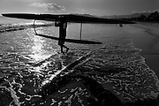 A man walks out into the ocean with his outrigger canoe.